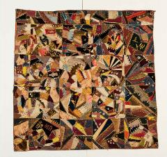 mosaic-style quilt with dark colors and sharp-edged triangular pieces