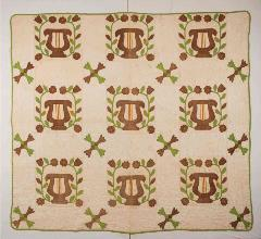 patterned quilt with multiple lyres encased in floral foliage