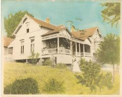 picture of house with front porch, trees, and woman in yard