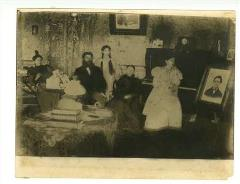 sepia-toned photo of family in den with piano