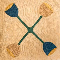 yellowed quilt with green x-shape and blue and tan endings