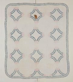 white quilt with blue circular pattern enclosed with diamond shapes and pink petal-like ends
