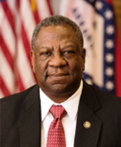 headshot of man in jacket with red tie with u.s. flag and arkansas flag in background